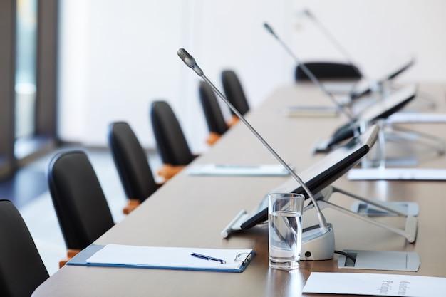 Изображение пустого стола с документами и микрофонами в зале заседаний