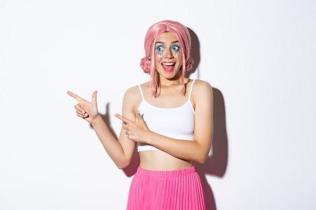 ピンクのかつらとハロウィーンの化粧をした熱狂的なパーティーガールの画像。幻想的なものを見て、指を左に向け、白い背景の上に立っています。