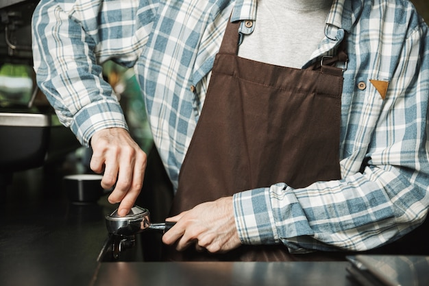 屋外のカフェや喫茶店で働いているときにコーヒーを作るエプロンを着ているヨーロッパのバリスタ男性の画像