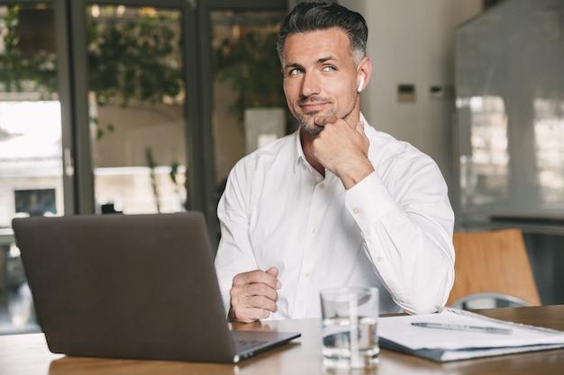 사무실 테이블에 앉아 흰색 셔츠를 입고 무선 이어 버드를 사용하여 노트북에서 일하는 유럽 사업가 30 대의 이미지