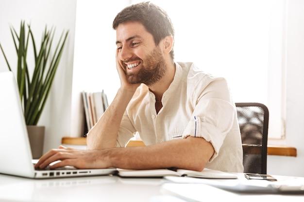 Изображение европейского бизнесмена 30-х годов в белой рубашке, работающего с ноутбуком и бумажными документами, сидя в современном офисе