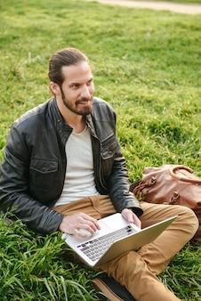 Изображение европейского стильного парня в кожаной куртке, сидящего на траве в зеленом парке и использующего серебряный блокнот