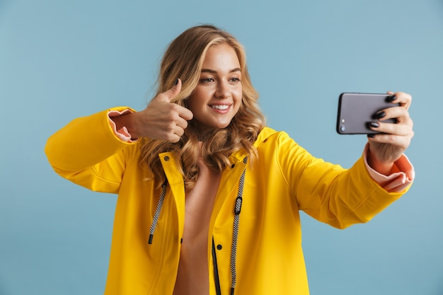 携帯電話を持って自分撮り写真を撮る黄色いレインコートを着ている20代のヨーロッパの女性の画像