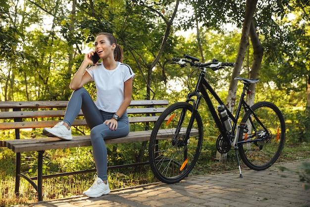 Изображение европейской женщины, сидящей на скамейке в парке с велосипедом и разговаривающей по мобильному телефону