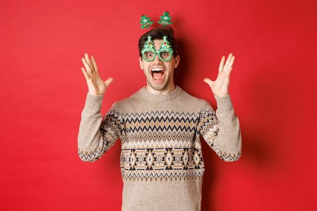 パーティーグラス、クリスマスセーター、手を上げて大きな発表をし、新年のお祝い、赤い背景を楽しんでいる興奮して驚いた白人男性の画像。
