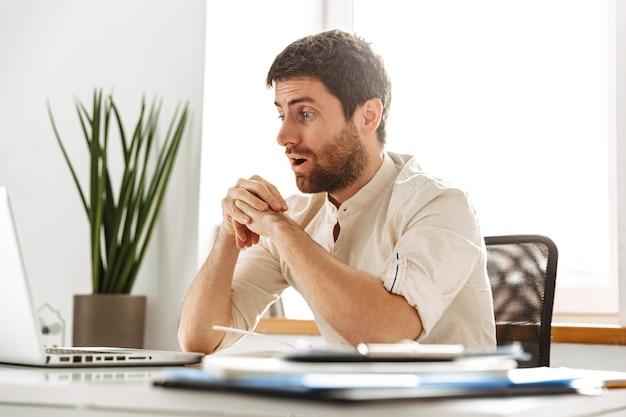 Изображение возбужденного бизнесмена 30-х годов в белой рубашке, работающего с ноутбуком и бумажными документами, сидя в современном офисе