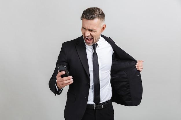 携帯電話を見て、孤立した勝利を祝うフォーマルなスーツを着た興奮した白人ビジネスマンの画像