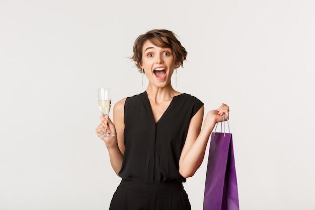 선물 쇼핑 가방을 들고 샴페인을 마시고, 즐겁게 웃고, 뭔가 축하하는 흥분된 우아한 여자의 이미지.