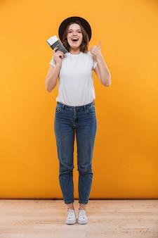 Изображение возбужденного эмоционального молодого туриста женщины, стоящего изолированно на желтом фоне, холдинг паспорт с билетами, глядя на камеру, делает большие пальцы руки вверх.