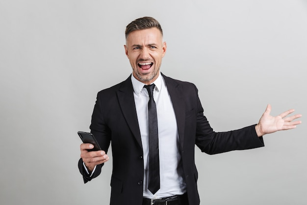 携帯電話で入力し、孤立した勝利を祝うフォーマルなスーツで興奮したハンサムなビジネスマンの画像