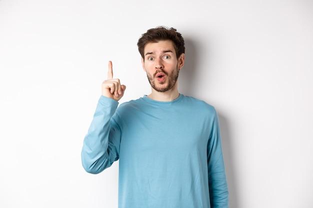아이디어를 피칭, 손가락을 높이고 흰색 배경 위에 서있는 유레카 말하는 흥분된 잘 생긴 남자의 이미지.