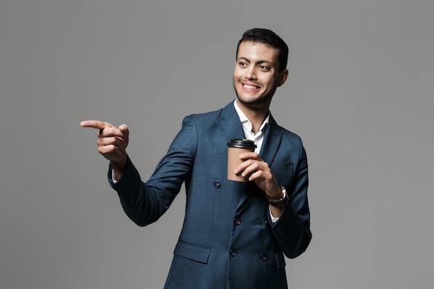 Изображение возбужденного счастливого бизнесмена позирует изолированного над серой стеной, пить кофе указывая.