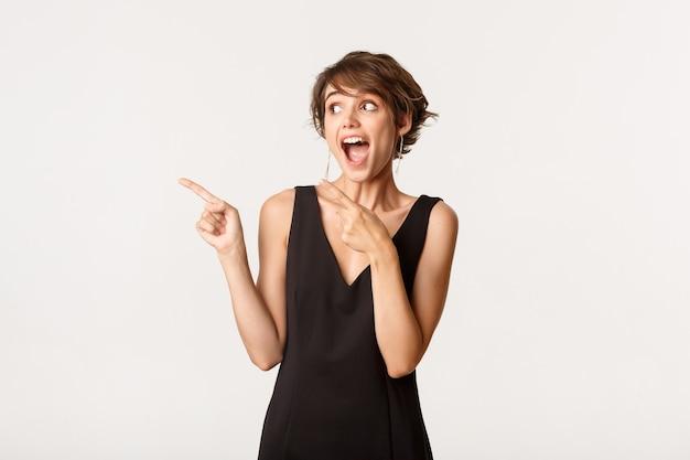 뭔가 멋진 것에 반응하는 흥분된 행복 한 여자의 이미지, 흰색 위에 서있는 로고에서 왼쪽 손가락을 가리키는.