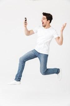Изображение возбужденного счастливого молодого человека представляя изолированное над белой стеной, используя прыжки мобильного телефона.