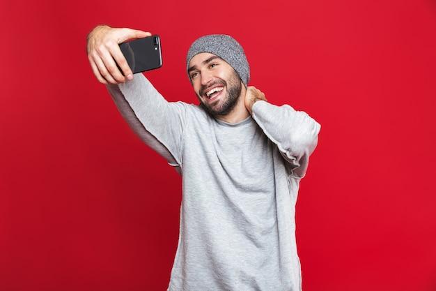 Изображение возбужденного мужчины 30-х годов в повседневной одежде, смеющегося во время селфи на мобильном телефоне