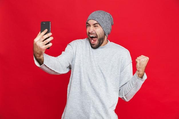 수염과 콧수염 서있는 동안 스마트 폰을 들고 흥분된 남자 30 대의 이미지, 절연