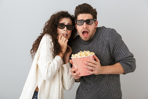 Изображение возбужденных мужчины и женщины в 3d-очках, держащих ведро с попкорном, изолированные на серой стене