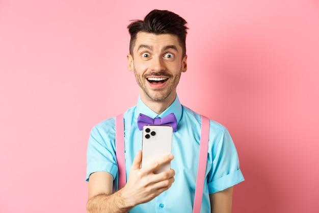 興奮した男性がオンラインでプロモーションオファーをチェックし、スマートフォンを持ってカメラを見て驚いて、ピンク色で幸せに立っている画像。
