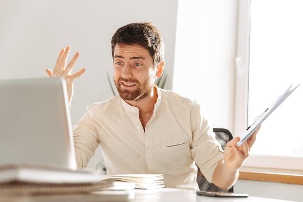 Изображение возбужденного офисного работника 30-х годов в белой рубашке с ноутбуком и бумажными документами, сидящего за столом на современном рабочем месте