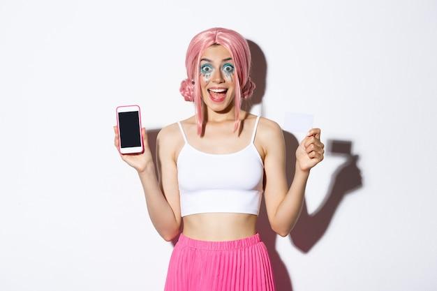 ピンクのかつらとハロウィーンの衣装でクレジットカードとスマートフォンのスクリードを示す興奮したパーティーガールの画像...