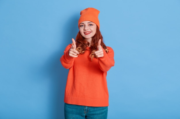 고립 된 카메라에서 손가락을 가리키는 흥분된 빨간 머리 여자의 이미지.