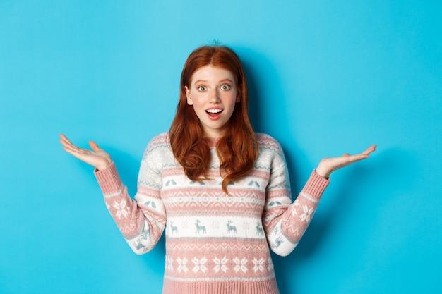 흥분한 빨간 머리 소녀의 이미지는 좋은 소식에 반응하고 놀란 표정을 하고 손을 옆으로 벌리고 웃고 파란 배경에 겨울 스웨터를 입고 서 있습니다.