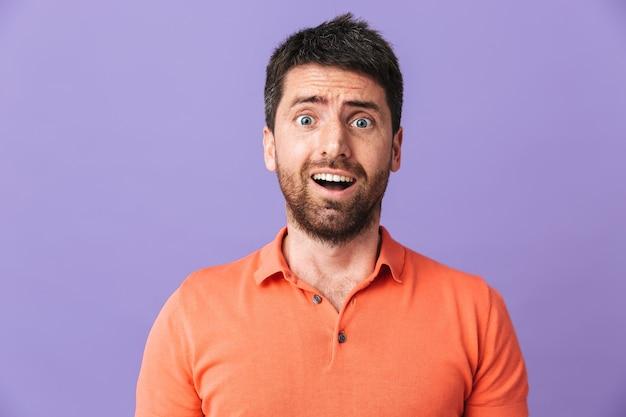Изображение возбужденного потрясенного эмоционального молодого красивого бородатого мужчины, позирующего изолированно над фиолетовой стеной.