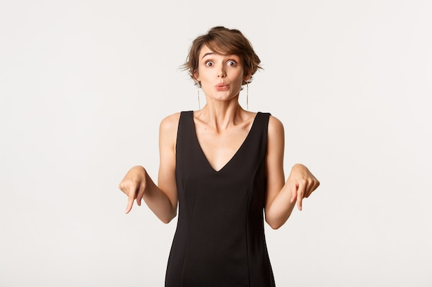 Изображение возбужденной стильной брюнетки женщины указывая пальцами вниз и любопытно смотрят на камеру, стоя над белой.