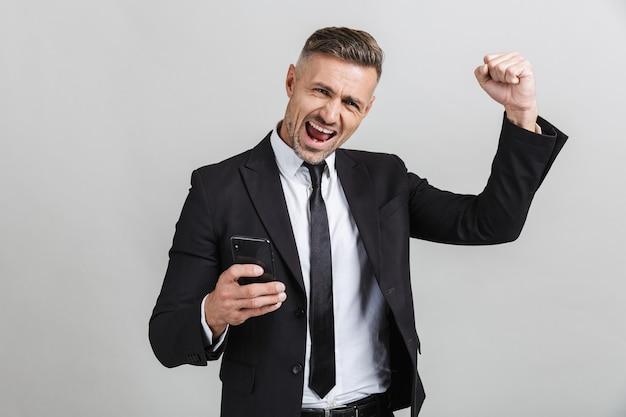 Изображение возбужденного небритого бизнесмена в строгом костюме, печатающего на мобильном телефоне и сжимающего кулак изолированы