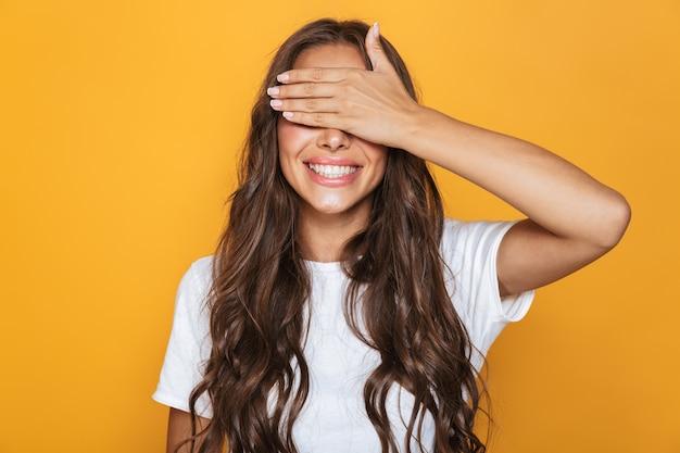 黄色の壁に隔離された、笑顔で目を覆っている長い髪の20代の興奮した女性の画像