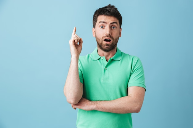 Изображение возбужденного молодого красивого бородатого мужчины, позирующего изолированно над синей стеной, имеет идею.