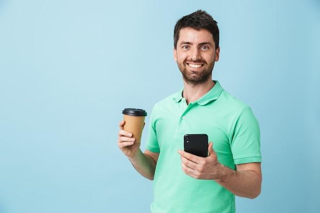 Изображение возбужденного молодого красивого бородатого мужчины, позирующего изолированно над голубой стеной, держащей чашку кофе с помощью мобильного телефона.