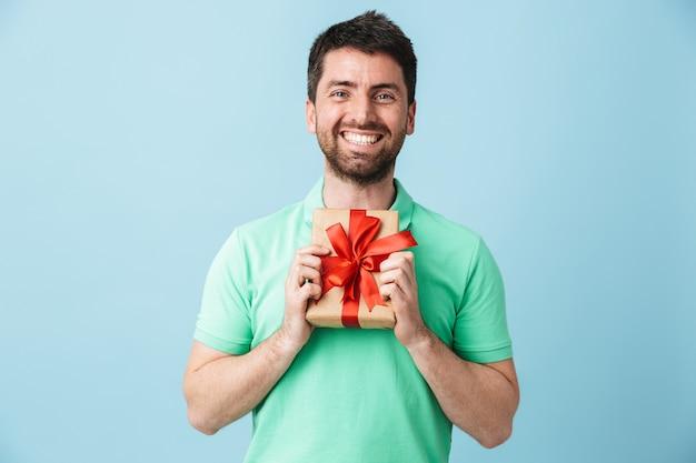 Изображение возбужденного молодого красивого бородатого мужчины, позирующего изолированно над голубой стеной, держащей подарочную коробку.