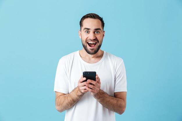Изображение возбужденного молодого счастливого бородатого человека, позирующего изолированным над синей стеной, с помощью мобильного телефона в чате. летняя концепция.