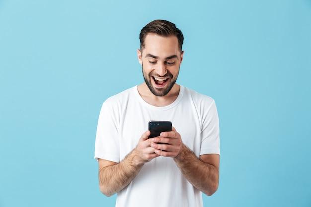Изображение возбужденного молодого счастливого бородатого человека, позирующего изолированным над синей стеной, с помощью мобильного телефона в чате.