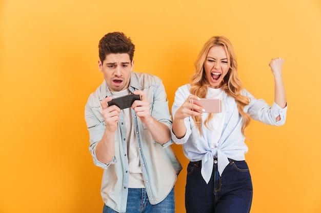 흥분된 젊은 남자와 여자가 함께 놀고 스마트 폰에서 비디오 게임에서 경쟁하는 이미지