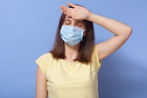 体調不良、感染した病気の若い女性、コロナウイルス感染症、額に手を当て、目を閉じている、防護マスクに入っている、発熱している、の画像。コロナウイルスの発生の概念。
