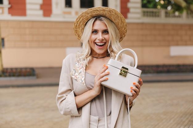 도시 거리를 걷는 동안 그녀의 세련된 지갑을 보여주는 양복과 밀짚 모자를 쓰고 멋진 여자의 이미지