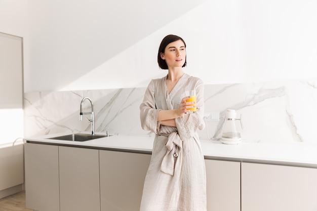 Образ очаровательной женщины с короткими темными волосами, стоящей на кухне и пьющей апельсиновый сок из прозрачного стекла
