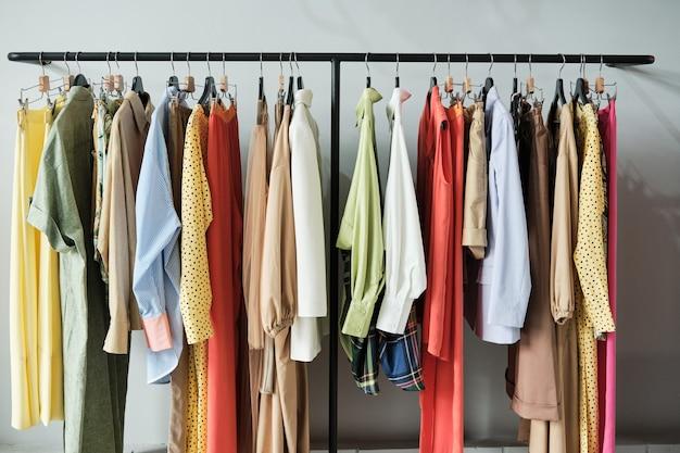 Изображение модных платьев и рубашек, висящих на вешалке в магазине одежды
