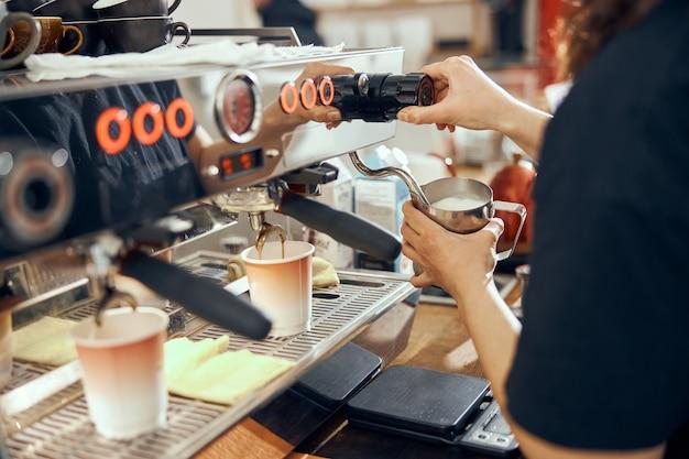 커피 메이커를 사용하여 카페에서 우유를 찌는 여성 바리 스타의 이미지.