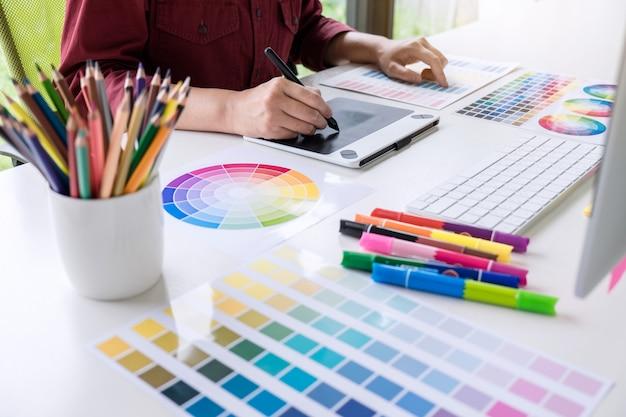 色の選択に取り組んでいるとグラフィックタブレットで描く女性の創造的なグラフィックデザイナーのイメージ Premium写真