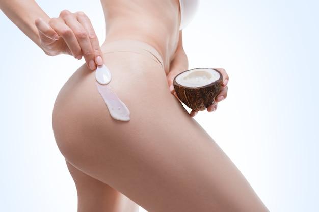 엉덩이에 천연 코코넛 크림을 적용하는 여성 손의 이미지. 의료 개념. 셀룰 라이트 방지 연고. 혼합 매체