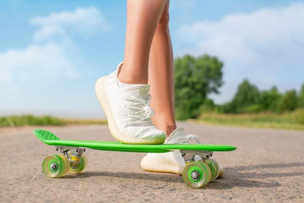 Изображение женских ножек со скейтбордом. концепция отдыха и развлечений. спорт. смешанная техника