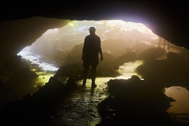 Изображение фигуры тени, стоящей в отверстии пещеры (женщина)