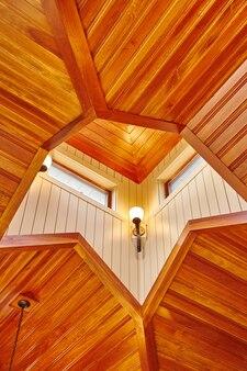 天井上部の天窓から放射状に広がるオーク材のオレンジ色に見える木片を備えた、完成した派手な外観の木製天井の画像