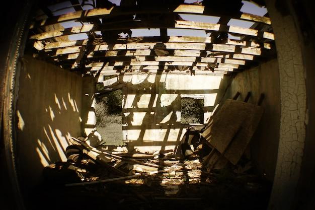 廃墟となった建物の茶色の老朽化した部屋の魚眼レンズの画像。露出した屋根から日光が差し込む。