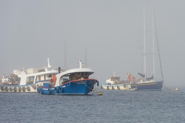 Изображение рыбацких лодок, стоящих на якоре в туманную погоду