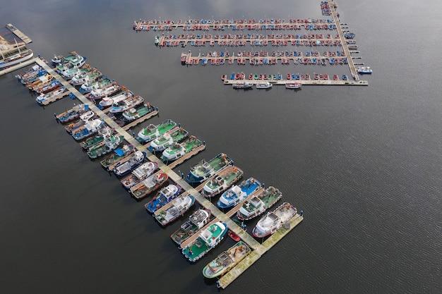 Изображение рыбацких лодок на пристани в порту с воздуха