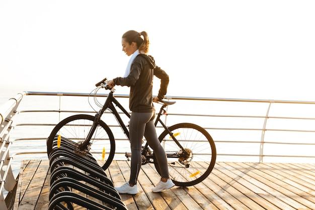 Изображение фитнес-женщины, стоящей с велосипедом на променаде, во время восхода солнца над морем